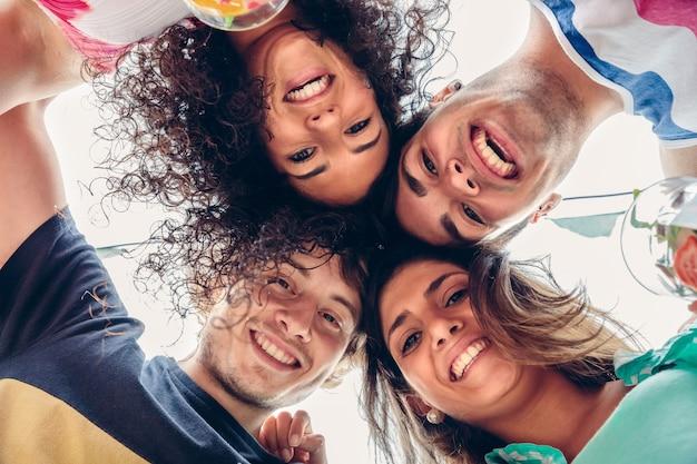Gros plan de jeunes gens heureux avec leurs têtes ensemble s'amusant dans une fête d'été. concept de mode de vie des jeunes. vue d'en bas.