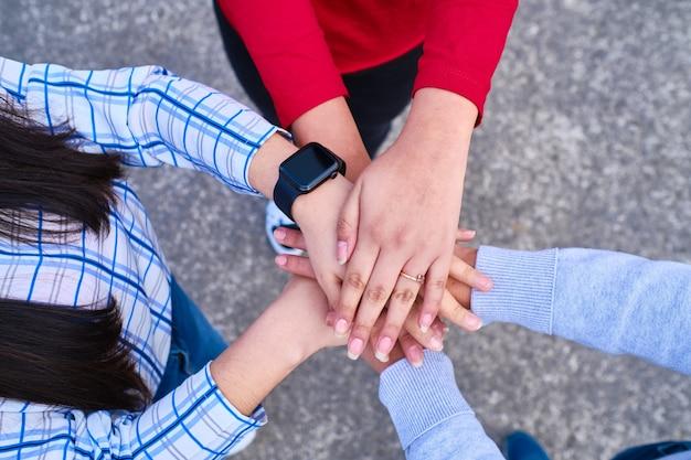 Gros plan de jeunes gens mettant leurs mains ensemble