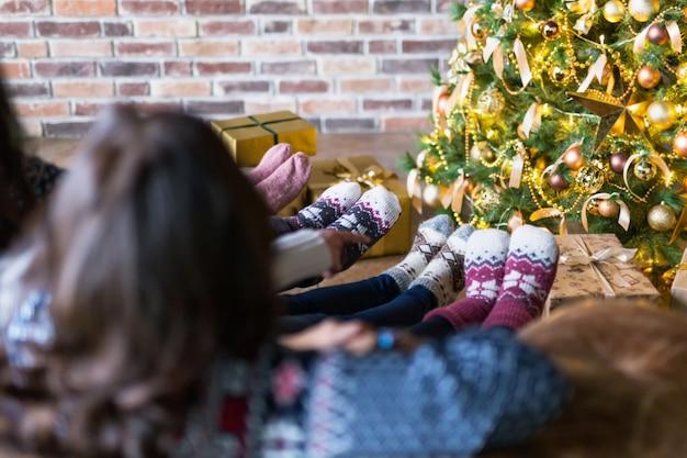 Gros plan, de, jeunes, habillé, dans, noël, chaussettes, séance, près, arbre noël, à, boîtes cadeau