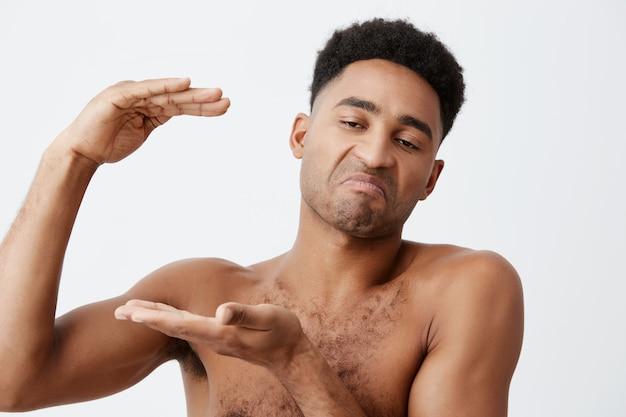 Gros plan de jeunes hommes drôles à la peau noire avec des cheveux bouclés sans vêtements gesticulant avec les mains, montrant une grande taille, regardant de côté avec une expression cynique.
