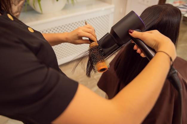 Gros plan des jeunes mains féminines tenant un sèche-cheveux et une brosse ronde professionnelle