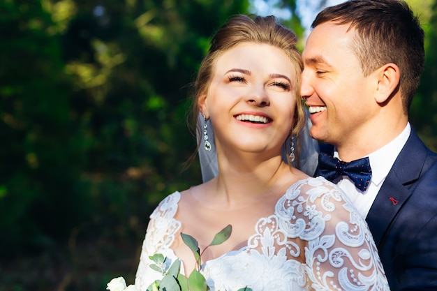 Gros plan de jeunes mariés heureux dans les bras les uns des autres et de doux sourires