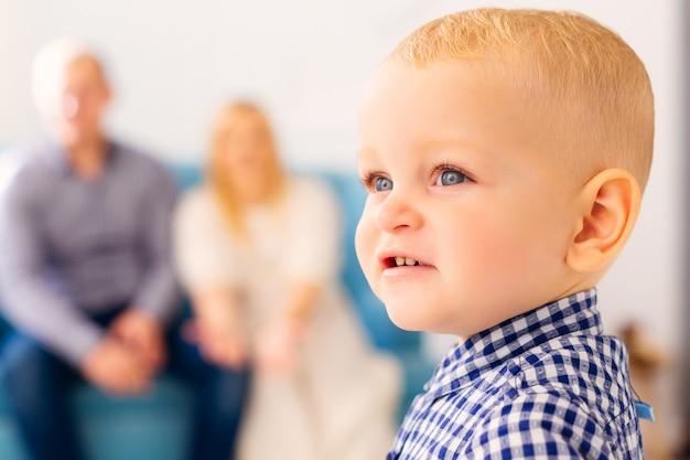 Un gros plan d'un joli petit garçon avec leurs parents