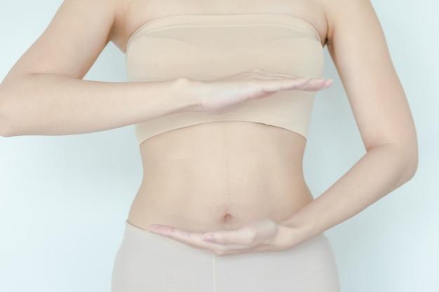 Gros plan d'un joli ventre de femme enceinte mince avec la main dessus