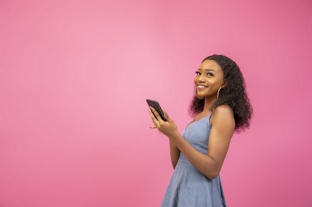 Gros plan d'une jolie femme dans une ambiance excitante tenant son téléphone