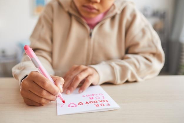 Gros plan d'une jolie fille afro-américaine signant une carte faite à la main comme cadeau pour la fête des pères, espace pour copie