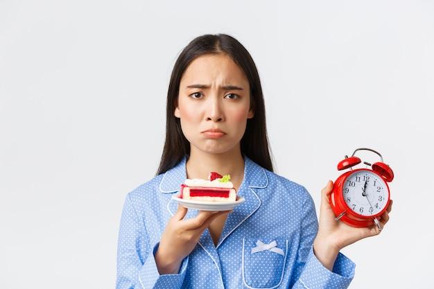 Gros plan d'une jolie fille asiatique boudeuse en pyjama montrant une horloge et regardant avec regret et tentation un délicieux morceau de gâteau, voulant un dessert mais il est trop tard, debout sur fond blanc