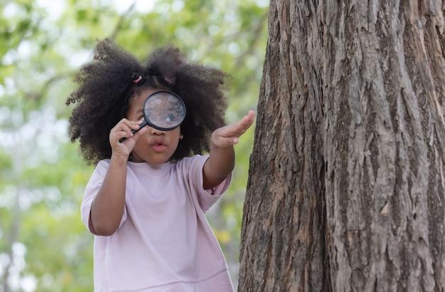 Gros plan sur une jolie fille aux cheveux bouclés afro regardant un arbre à travers une loupe