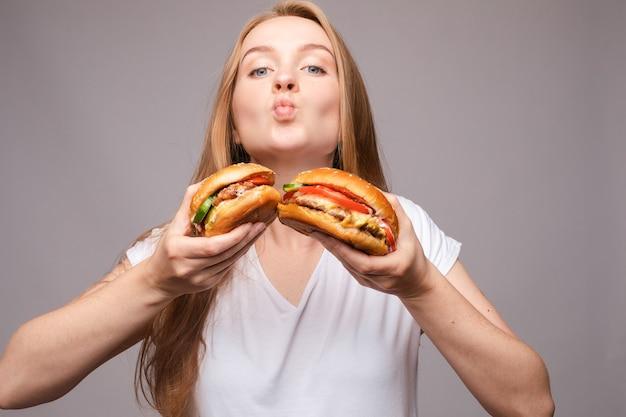 Gros plan d'une jolie fille aux cheveux longs mordant un délicieux hamburger avec du poulet et de la salade, regardant la caméra sur fond rose. concept de restauration rapide américain.
