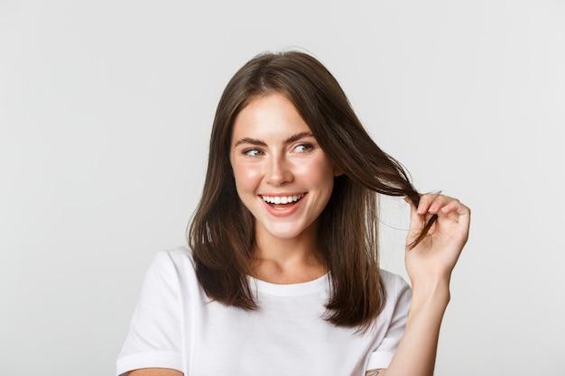 Gros plan d'une jolie fille brune séduisante jouant avec une mèche de cheveux, souriant et à la recherche intriguée vers la droite.