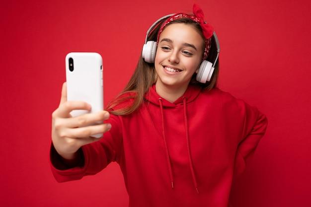 Gros plan d'une jolie fille brune souriante portant un sweat à capuche rouge isolé sur fond rouge tenant