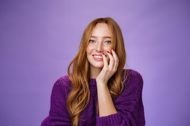 Gros plan d'une jolie fille rousse féminine et glamour avec des taches de rousseur en pull tricoté violet tenant la main sur la joue en riant doucement et en souriant largement à la caméra sur fond violet.