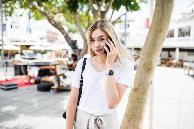 Gros plan d'une jolie fille souriante, parler au téléphone tout en se tenant à l'extérieur sur une rue de la ville