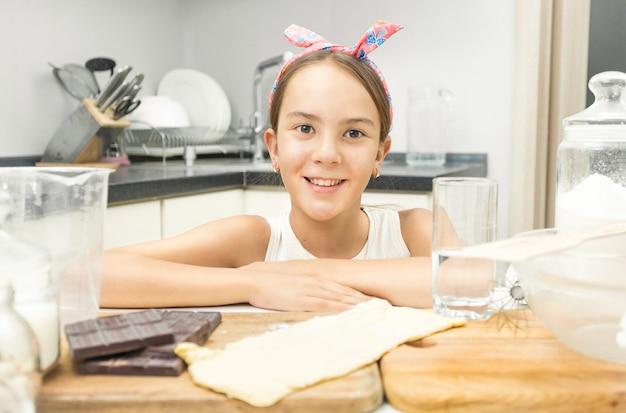 Gros plan jolie fille souriante s'appuyant sur une planche de cuisine en bois dans la cuisine