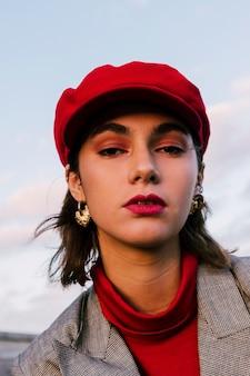 Gros plan d'une jolie jeune femme au bonnet rouge, regardant la caméra