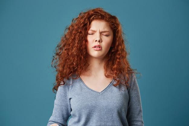 Gros plan de jolie jeune femme aux cheveux roux ondulés et taches de rousseur en chemise grise ayant des maux de tête après une nuit blanche.