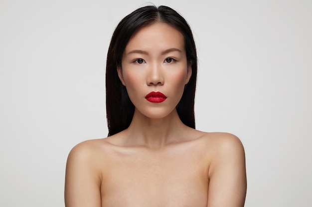 Gros plan de la jolie jeune femme brune avec un maquillage de fête gardant ses lèvres rouges pliées tout en regardant sérieusement, isolé sur un mur blanc