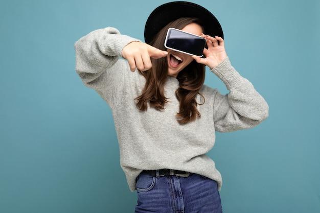 Gros plan d'une jolie jeune femme heureuse drôle portant un chapeau noir et un pull gris tenant un téléphone pointant le doigt vers la caméra isolée sur fond.