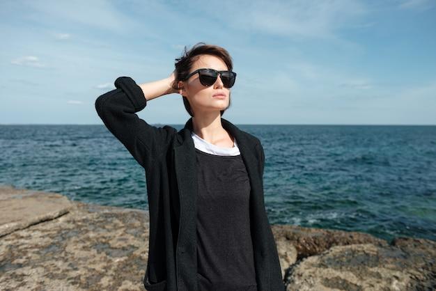 Gros plan de la jolie jeune femme à lunettes de soleil marchant au bord de la mer