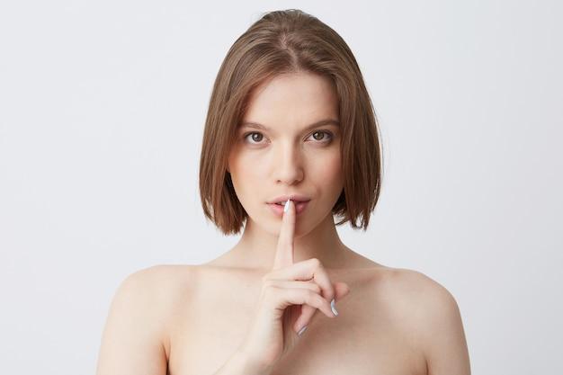 Gros plan de la jolie jeune femme nue aux cheveux longs va prendre une douche