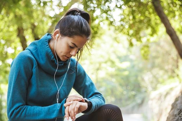 Gros plan d'une jolie jeune femme de remise en forme portant des vêtements de sport exerçant à l'extérieur, à l'aide de smartwatch