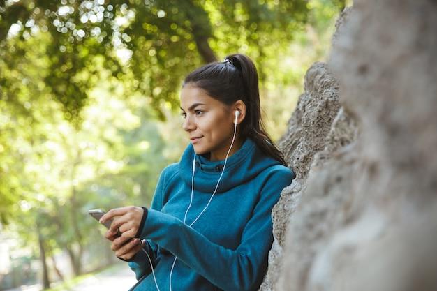 Gros plan d'une jolie jeune femme de remise en forme portant des vêtements de sport exerçant à l'extérieur, écoutant de la musique avec des écouteurs