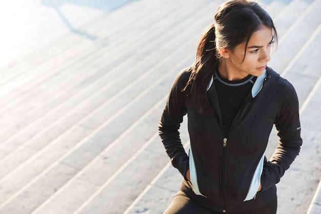 Gros plan d'une jolie jeune femme de remise en forme portant des vêtements de sport exerçant à l'extérieur, posant