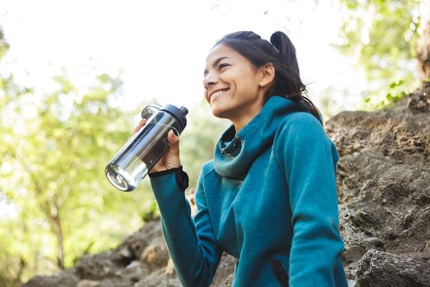 Gros plan d'une jolie jeune femme de remise en forme portant des vêtements de sport exerçant à l'extérieur, tenant une bouteille d'eau