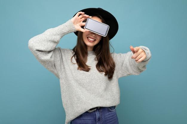 Gros plan d'une jolie jeune femme souriante et heureuse portant un chapeau noir et un pull gris tenant un téléphone pointant le doigt vers la caméra isolée sur fond. maquette, découpe, espace vide