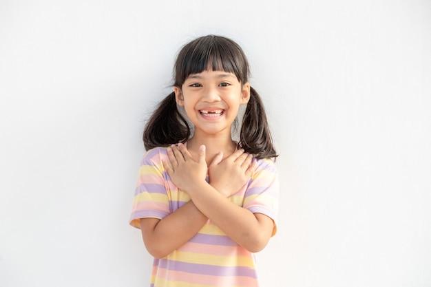 Gros plan d'une jolie petite fille heureuse isolée sur fond blanc tenir la main sur la poitrine du cœur se sentir reconnaissant, souriant petit enfant les yeux fermés prier remercier dieu hautes puissances, concept de foi