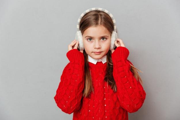 Gros plan d'une jolie petite fille en pull rouge et cache-oreilles