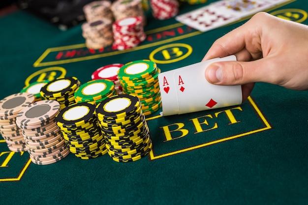Gros plan sur un joueur de poker masculin soulevant les coins de deux cartes as à la table de casino verte avec as