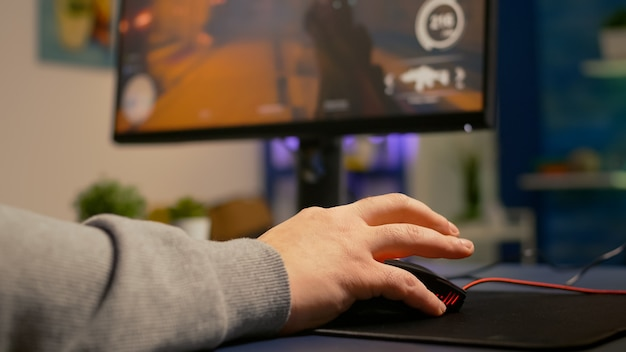 Gros plan sur un joueur utilisant une souris professionnelle jouant à un tournoi de tir à la première personne. joueur professionnel utilisant un équipement rvb pendant le championnat en ligne tard dans la nuit dans un studio de jeu