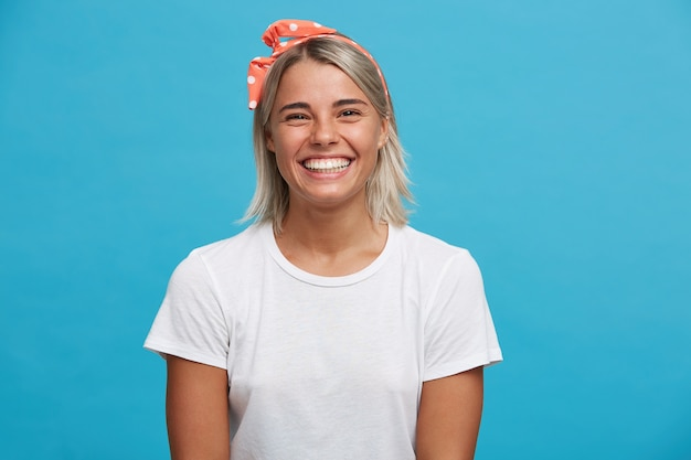 Gros plan de joyeuse charmante jeune femme blonde porte un t-shirt blanc