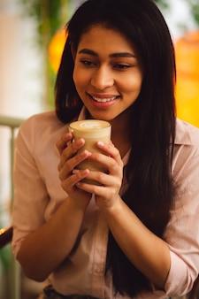 Gros plan d'une joyeuse femme aux cheveux noirs appréciant un délicieux café au lait et souriant tout en le tenant