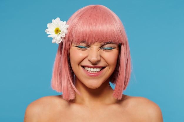 Gros plan de joyeuse jeune femme aux cheveux roses belle avec un maquillage de fête portant des fleurs dans sa tête tout en posant sur fond bleu, fronçant les sourcils tout en souriant joyeusement