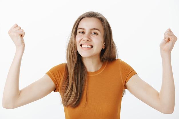 Gros plan de joyeuse jeune fille mignonne se réjouissant, levant les mains en signe de hourra, pompe de poing et souriant, triomphant de la victoire