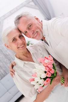Gros plan d'un joyeux couple de personnes âgées avec beau bouquet de fleurs de tulipes