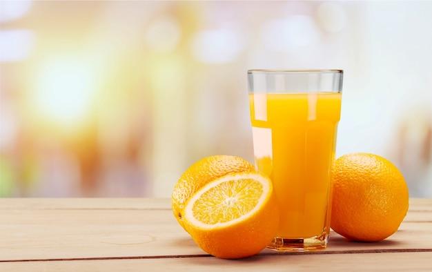 Gros plan de jus d'orange frais et savoureux en verre sur table