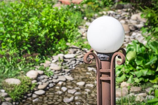 Gros plan de la lanterne décorative et pierres de galets. concept d'aménagement paysager.