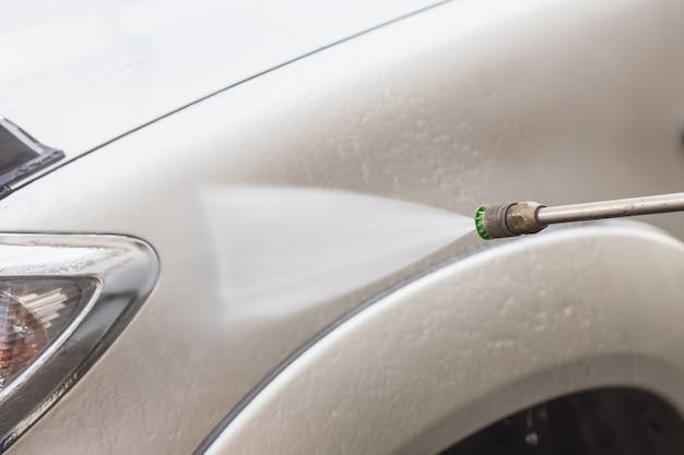 Gros plan de lavage de voiture avec jet d'eau à haute pression