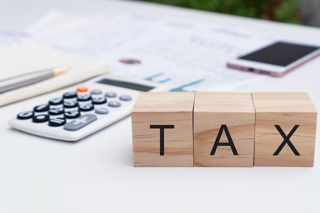 Gros plan de la lettre d'impôt sur le cube en bois, ordinateur portable, calculatrice, factures sur bureau blanc