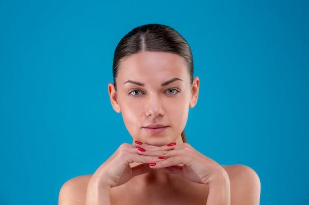 Gros plan des lèvres et des épaules de la jeune femme caucasienne avec maquillage naturel, peau parfaite et yeux bleus, isolés sur fond bleu. portrait en studio.