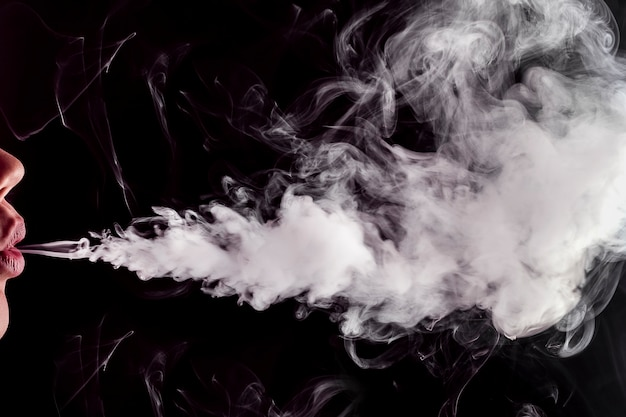 Gros plan des lèvres libérant de la fumée de vape (e-cigarette) avec un espace pour le texte