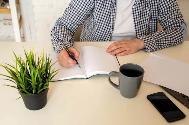 Gros plan sur le lieu de travail : des mains féminines prennent des notes dans un cahier sur un bureau, dans le contexte d'un ordinateur portable en état de marche. concept : formation, gestion d'entreprise, projet. bureau ou travail à domicile avec un ordinateur portable