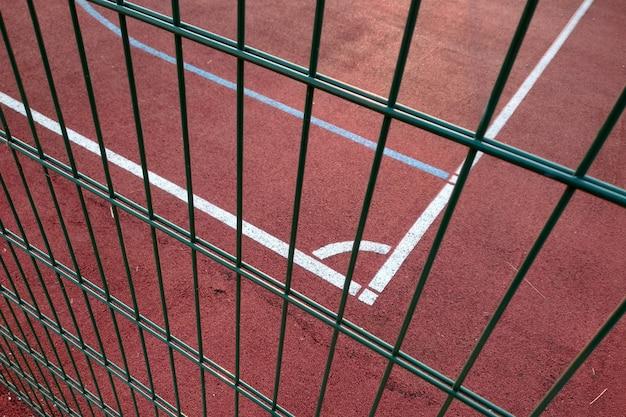 Gros plan des lignes de marquage blanches du terrain de basket extérieur clôturé avec une barrière de protection en métal.