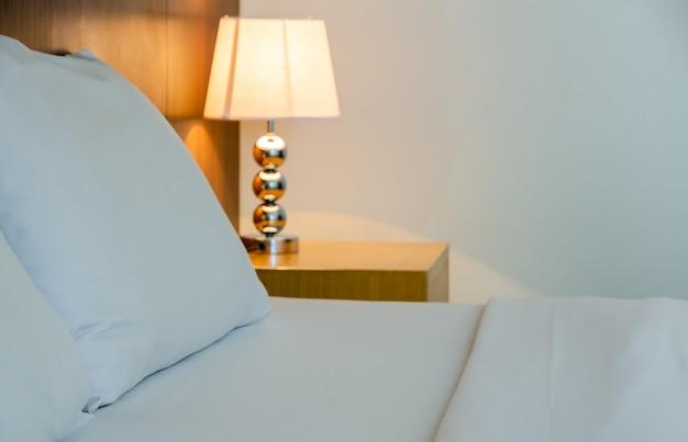 Gros plan d'un lit avec des draps blancs et lampe