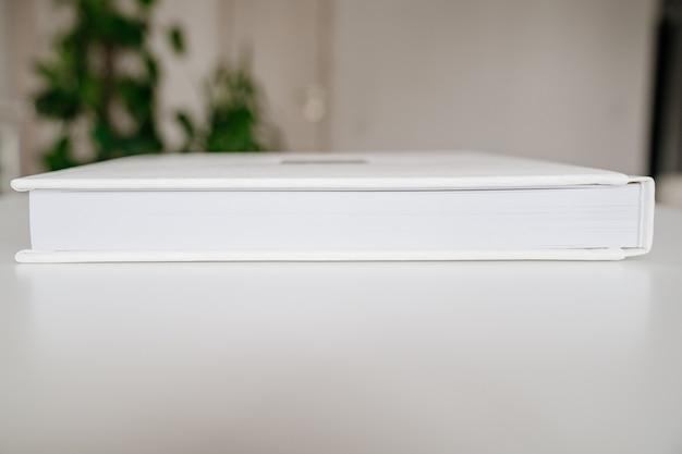 Gros plan sur un livre blanc de pages en plastique épais dans une reliure en cuir. produits d'impression. livres et albums photos. produits individuels.