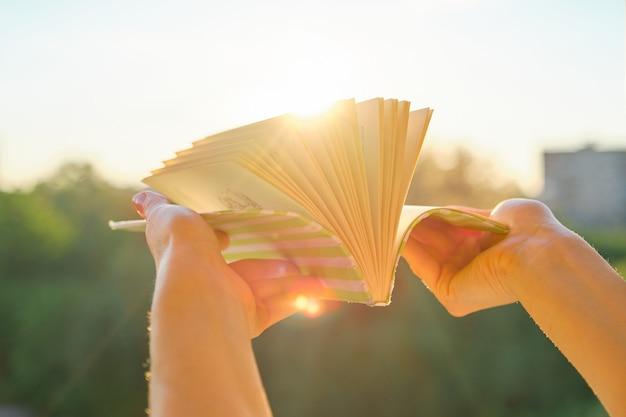 Gros plan, livre, womans, main, fond, coucher soleil