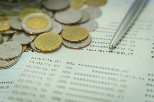Gros plan d'un livret de compte d'épargne avec un stylo et des pièces